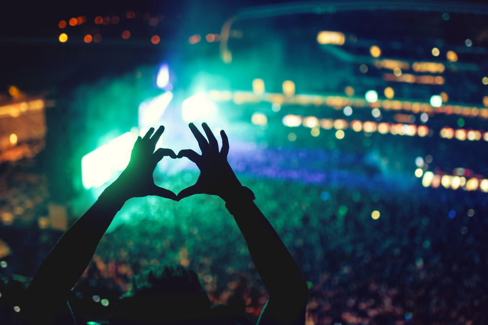 ライブ会場で手で作ったハートの形を掲げる人のシルエット