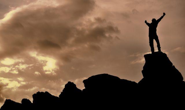 大きな岩の上でガッツポーズをする男性のシルエットと曇天
