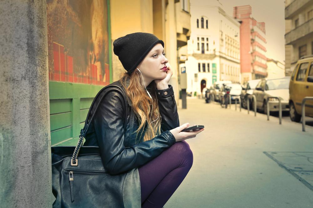 裏道に座り込む女性