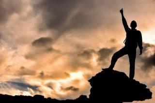 岩の上に立ちサムズアップする人のシルエット