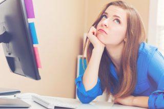 オフィスのデスクに肘をついて考え事をする女性