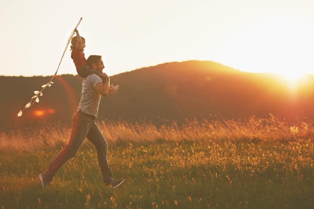 子供を肩車して草原を走る父親