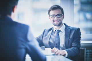 カフェの椅子に座る笑顔のビジネスマン