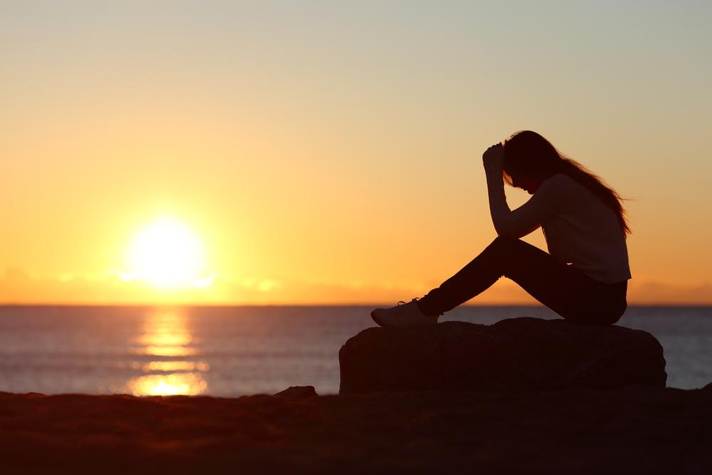 海岸に座り頭を抱える女性のシルエット