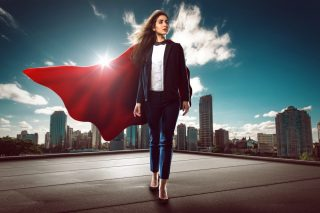 スーパーマンのマントをつけ颯爽と歩く女性