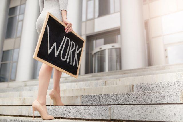 「WORK」と書かれた黒板を持って歩くハイヒールを履いた女性