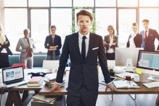 オフィスに立つ濃紺のスーツを着た男性と、背後に並ぶスーツ姿の人々