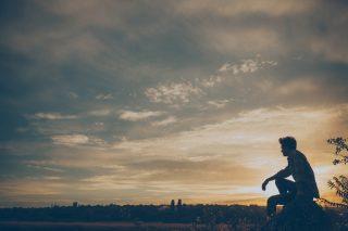 夕日をバックに草原とその先の森を見つめる男性