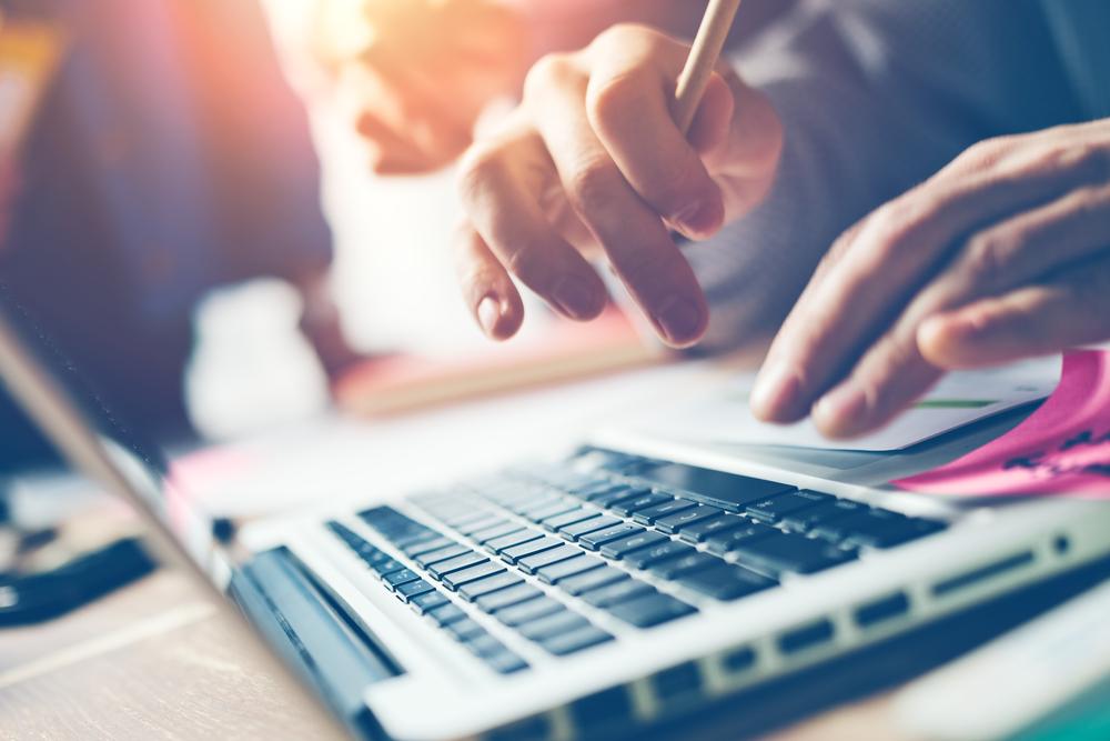 ノートパソコンを使って勉強する人の手元