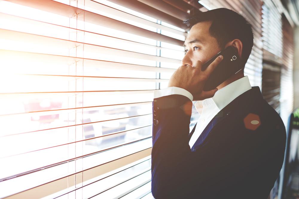 窓越しに電話するスーツの男性