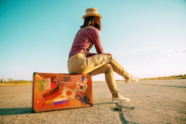 スーツケースに座り、地平線を見つめる女性