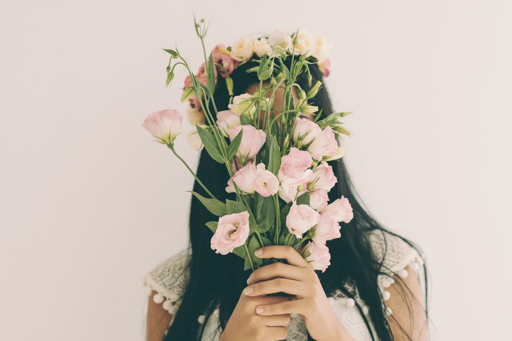 花輪を頭に被り、花束で顔を隠す女性