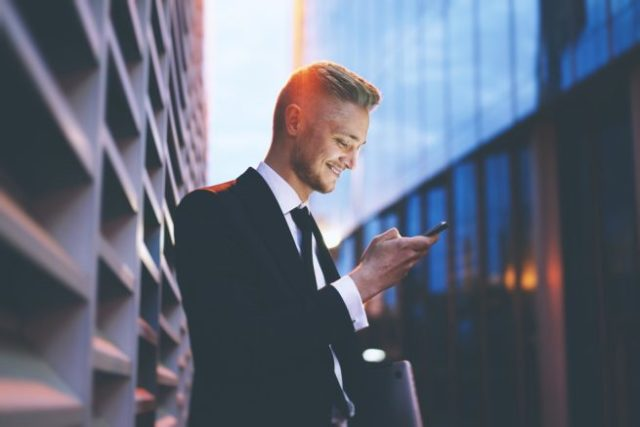 オフィス街でスマートフォンを見ながら微笑むスーツの男性