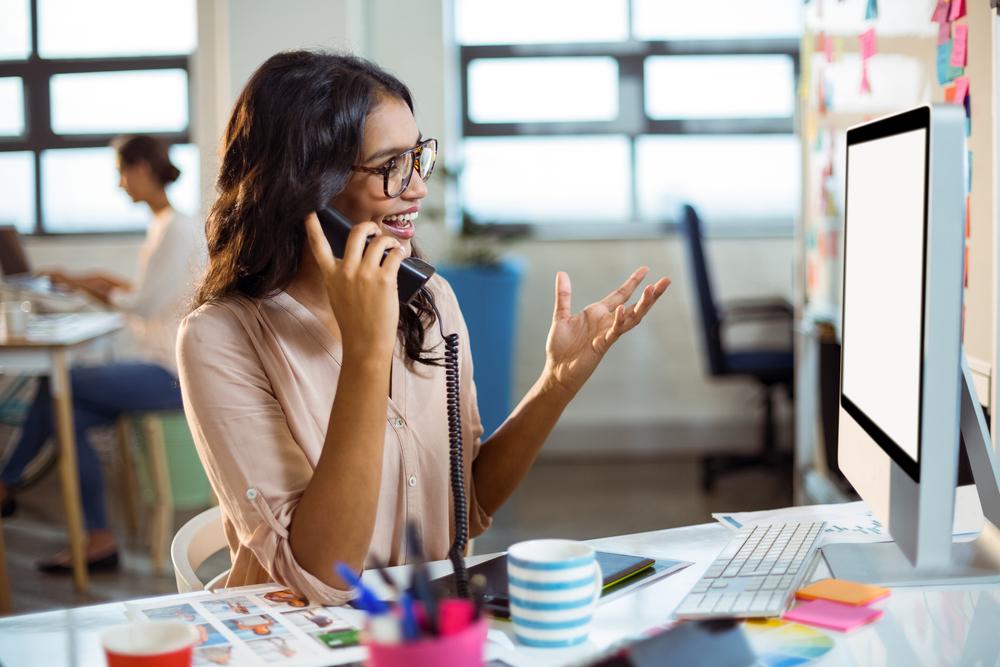 会社の内線電話で会話する笑顔の女性