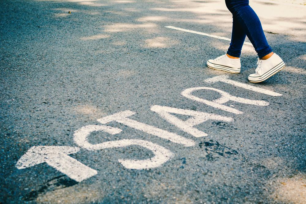 「START」と書かれた地面の上を歩く女性