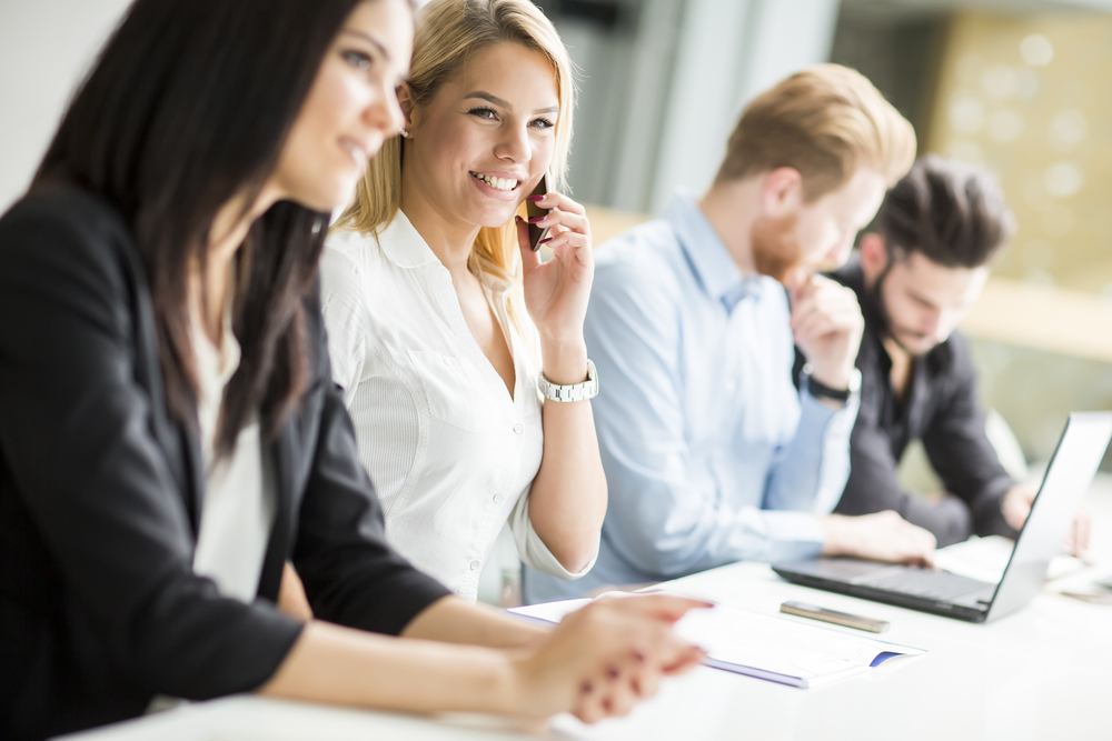 オフィスのデスクに座りながら笑顔で通話する女性