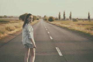 一本道を一人歩いていく女性