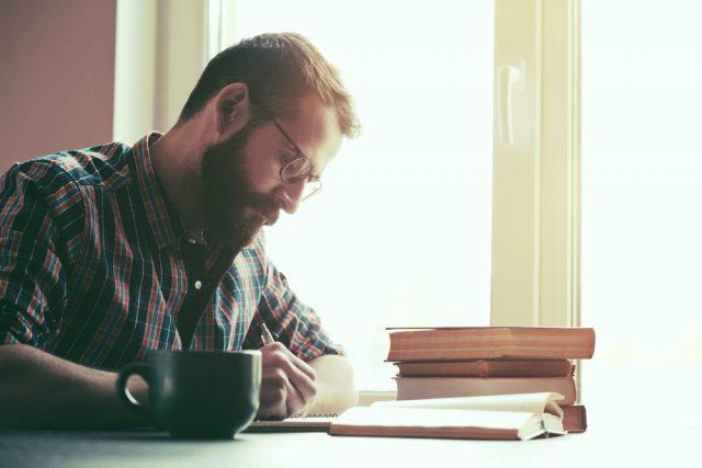 明るい窓辺で勉強するメガネをかけた男性
