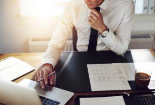 机に書類を広げ、ノートパソコンを見て考える黒いネクタイの男性