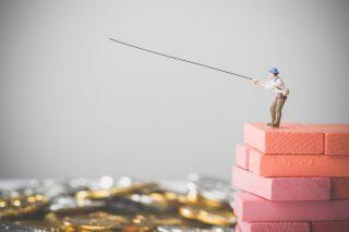 コインの海で釣りをする人の人形