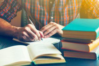 本を積み上げた机の上で勉強する男性