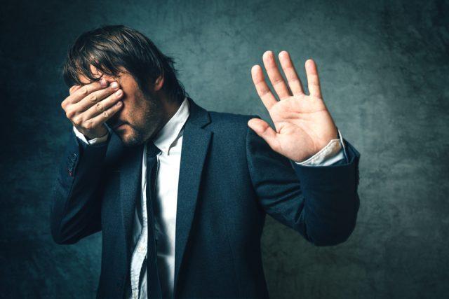 手で顔を覆い拒否のジャスチャーをする男性