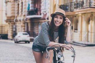 自転車にもたれかかり、こちらに笑顔を向ける髪の長い女性