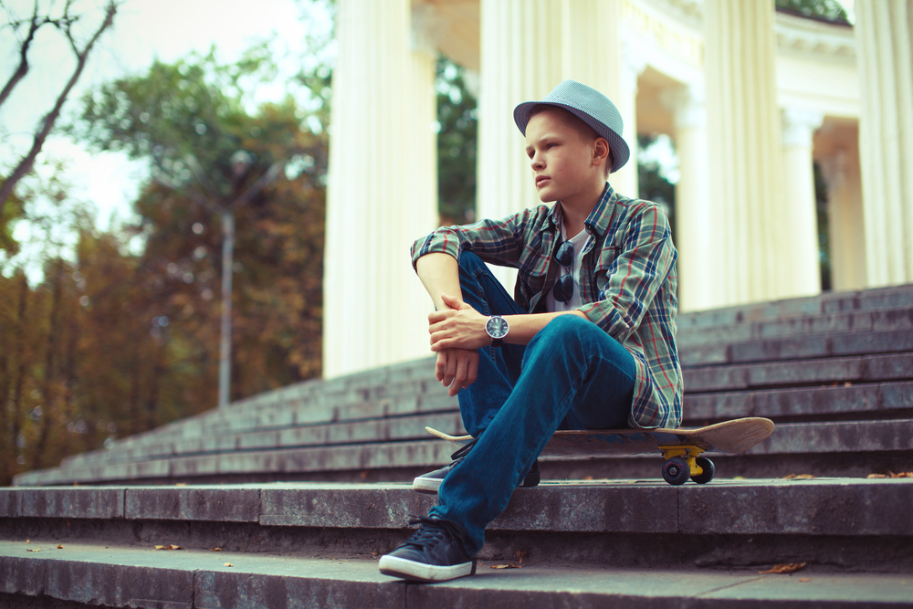 階段の上にスケートボードを置き座る少年