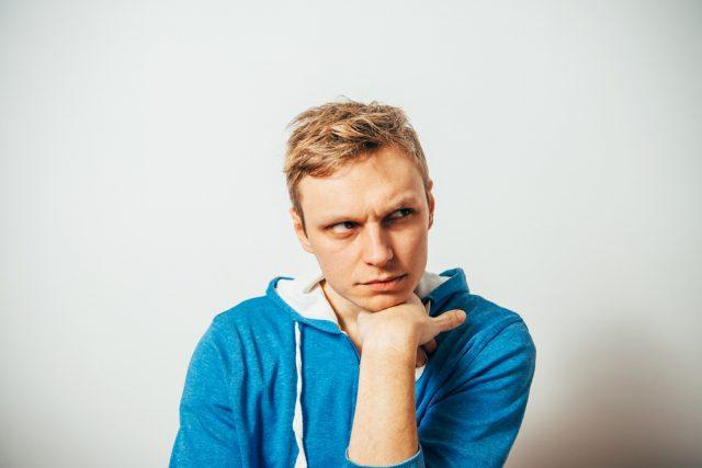 考え事をする青いパーカーを着た男性