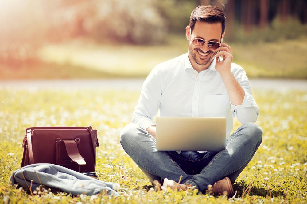 自由な格好で屋外で仕事をするサングラスをかけた男性