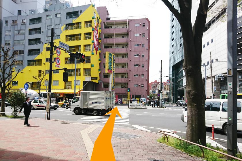 黄色い建物の「萬年屋」側に横断歩道を渡ります