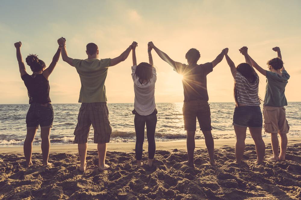 海辺で手を繋いでバンザイする人々