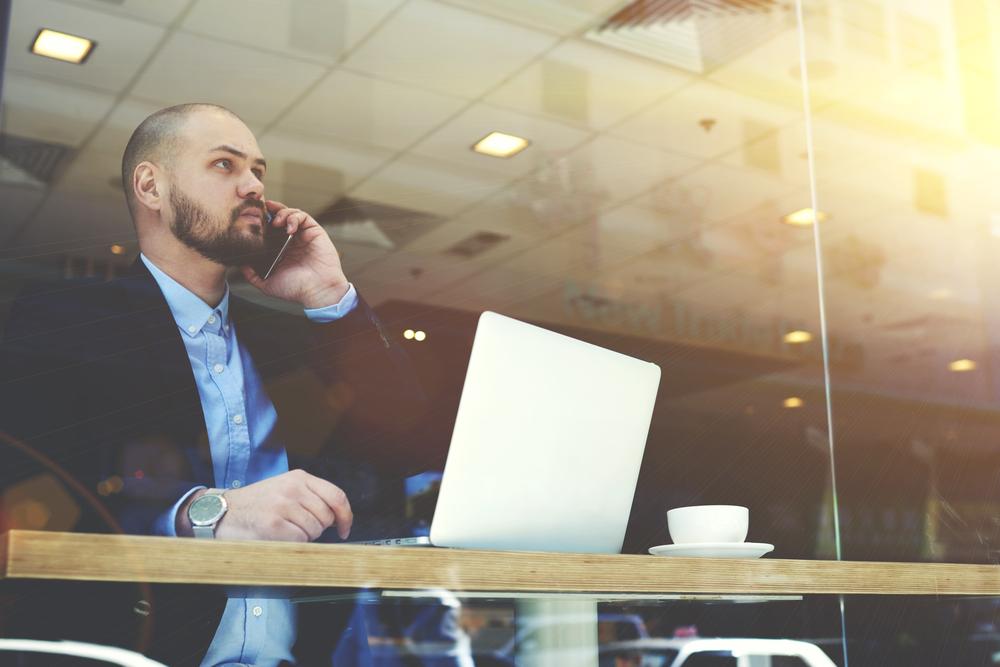 カフェで仕事中に電話をするジャケットを着た男性