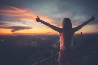 夕日に向かって手を大きく広げサムズアップする髪の長い女性