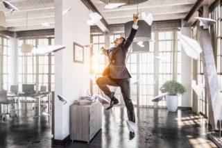 オフィスで飛び上がって喜ぶスーツの男性と、男性の周りを飛ぶ紙飛行機