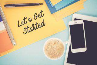 散らかった机の上と、そこに置かれた「let's get started」と書かれたファイル