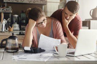キッチンで書類を見ながら考え込む男性と女性