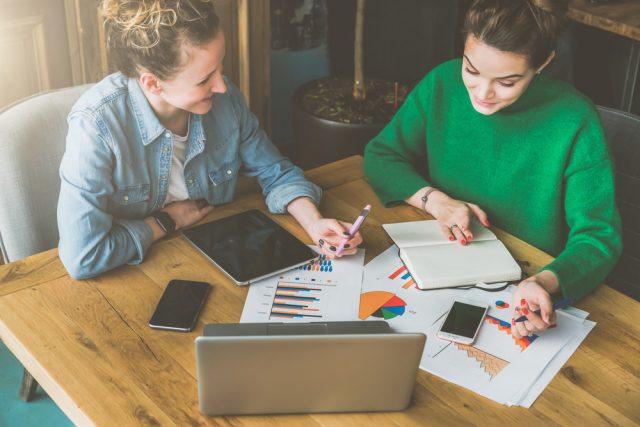 グラフの書かれた書類やノートパソコンを見ながら仕事する二人の女性
