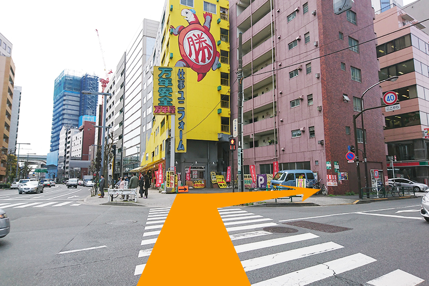 黄色い建物の「萬年屋」方面に横断歩道を渡り、右折します