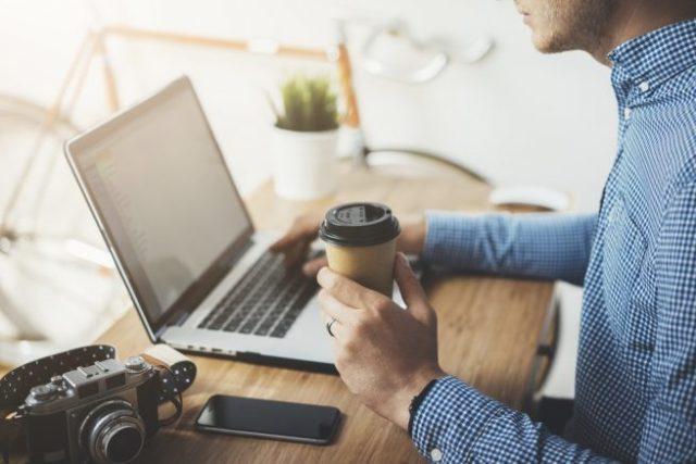 コーヒのテイクアウトカップを持ちながら仕事をする男性