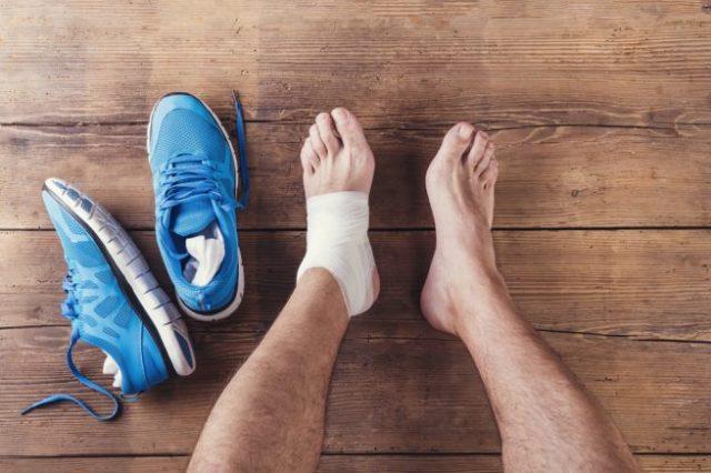 左足を負傷するアスリートと、その傍に無造作に置かれた運動靴