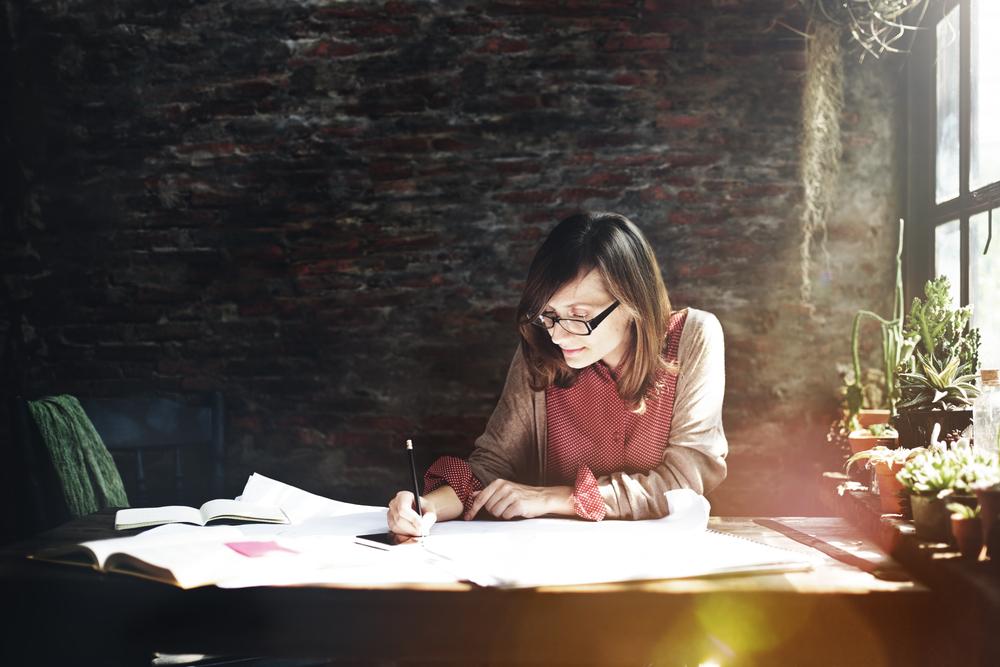 窓際でデザイン画を描くメガネをかけた女性