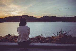 水辺に座りながら夕日を見つめる女性