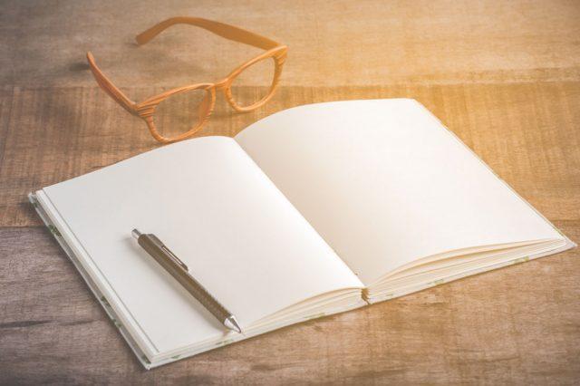 机の上に開かれたノートとペンとメガネ