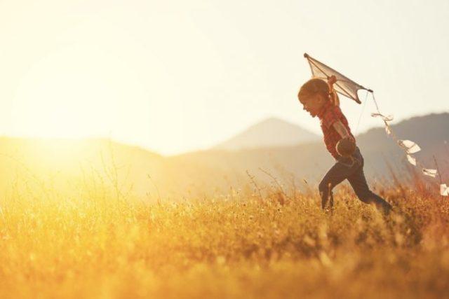夕日を背景にした、凧を飛ばそうとする少年