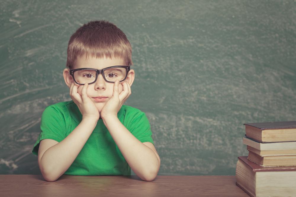 メガネをかけて本の横に座る少年