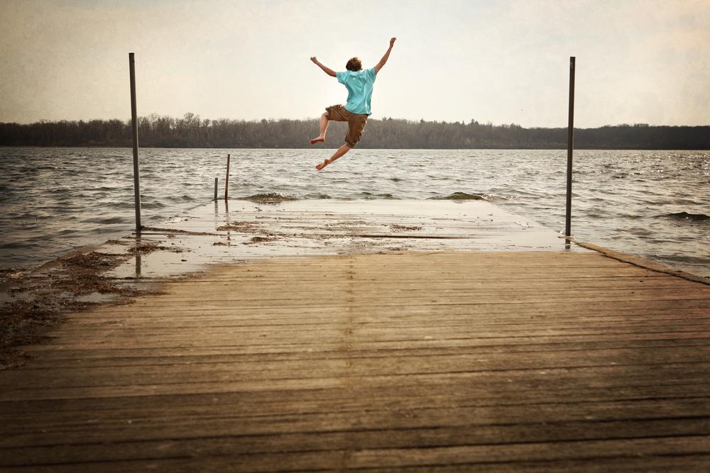 桟橋からジャンプして水の中に飛び込む男性
