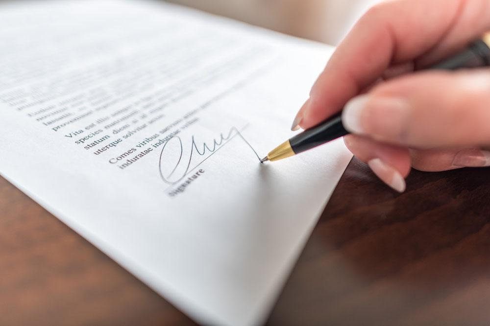 書類にサインする人の手元