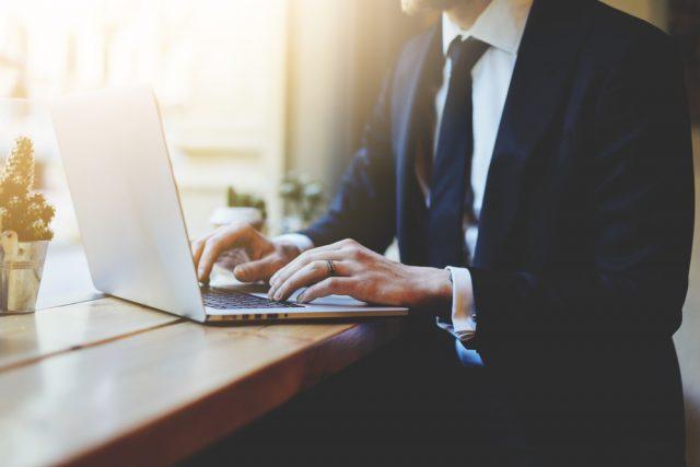 ノートパソコンを使う黒いスーツの男性