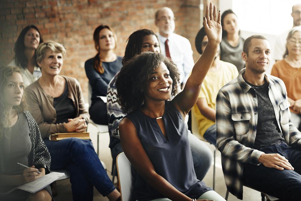 大勢の人の前で挙手する女性